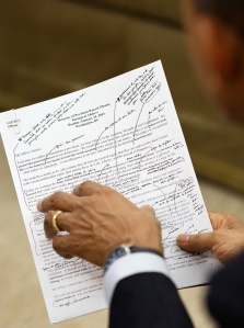 Obama holding pen and printed speech with heavily edit marks.
