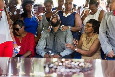 Black man, head thrown back and wailing in grief as family and loved ones try to console a father's grief.