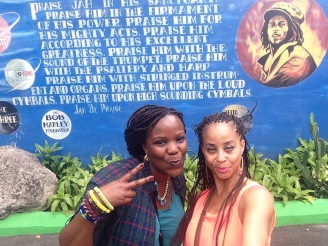 Two black women wearing braids taking a selfie in front of a Bob Marley mural